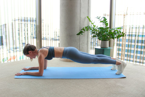 woman performing an elbow plank on an exercise mat