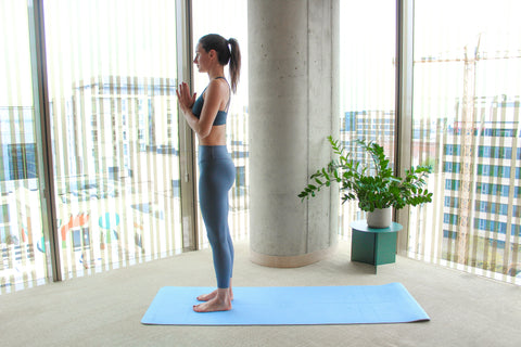 woman standing straight on yoga mat with hands together in front of the heart
