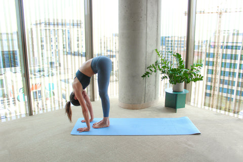 woman on yoga mat bending forward, with hands touching the floor