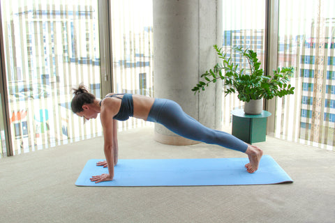 woman in high plank on yoga mat