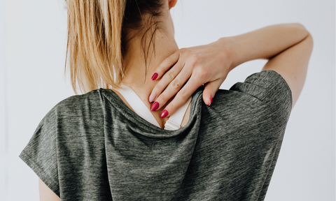 woman rubbing the back of her neck with her hand due to neck pain