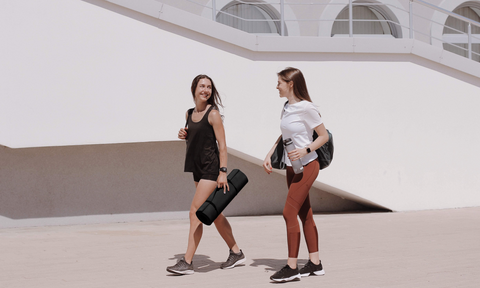two women laughing and walking side by side, one is holding a yoga mat while the other is holding a water bottle