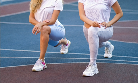 two women stretching their hamstrings on a tennis court
