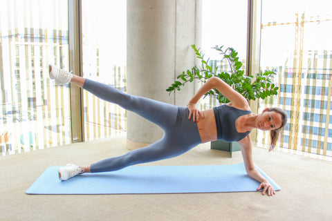 woman in a side plank position with leg lift