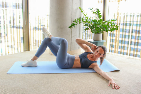 woman doing a crossover crunch with right elbow touching left knee