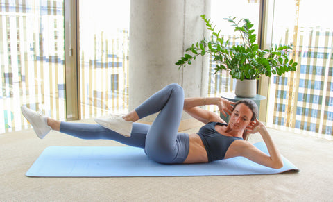 woman doing a bicycle crunch with right elbow touching left knee