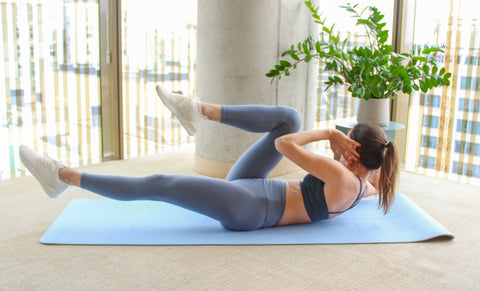 woman doing a bicycle crunch with left elbow touching right knee