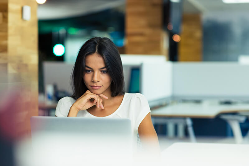 Woman on a laptop who could be researching when to start using retinol