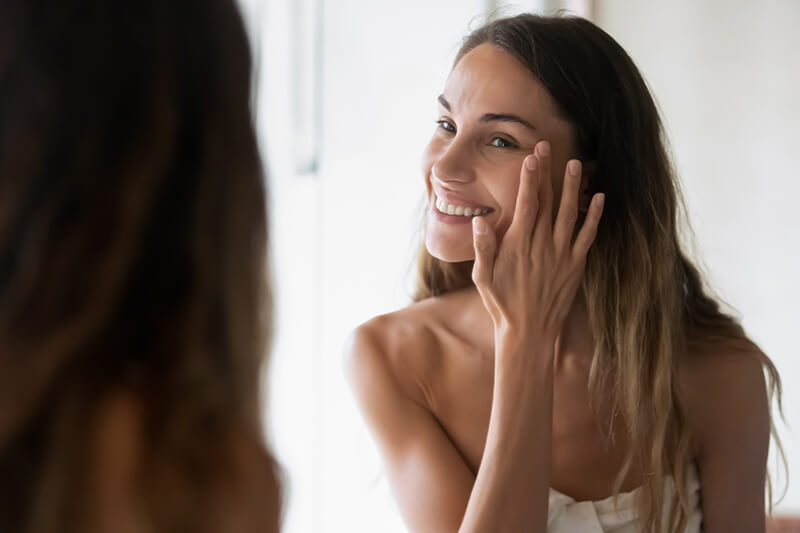 A woman using skincare in her nightly routine to prevent visible ageing