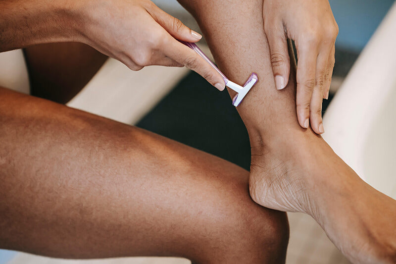 Woman shaving her leg can create ingrown hairs treatable with Body Smoothing System by SLMD Skincare