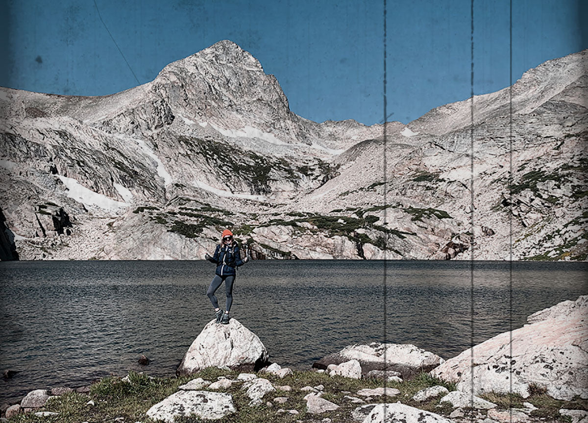 Erin Holberg hiking in front of a lake and mountains