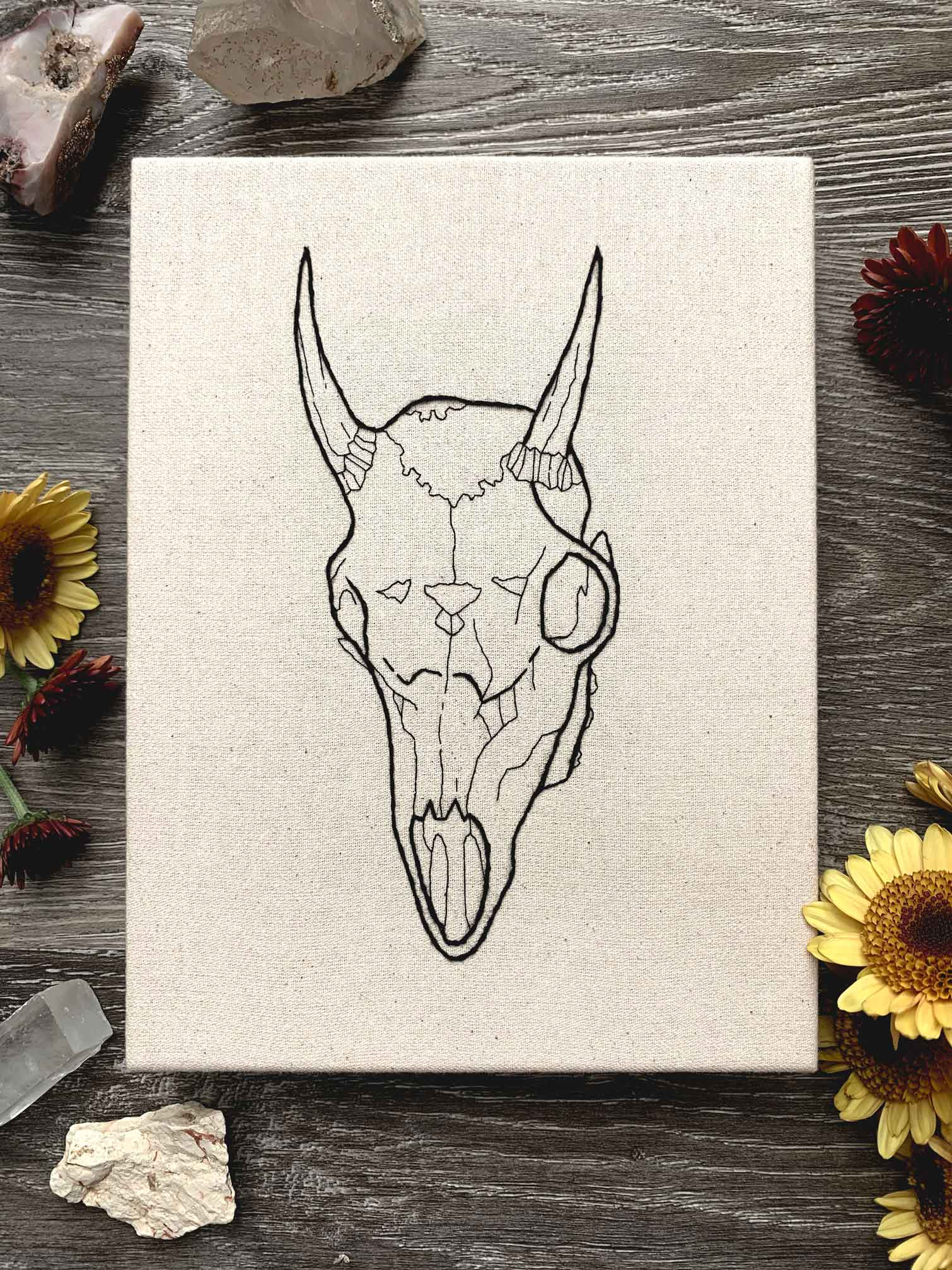 sewn embroidery of an animal goat skull