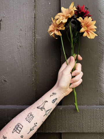 hand holding flowers and tattoo arm