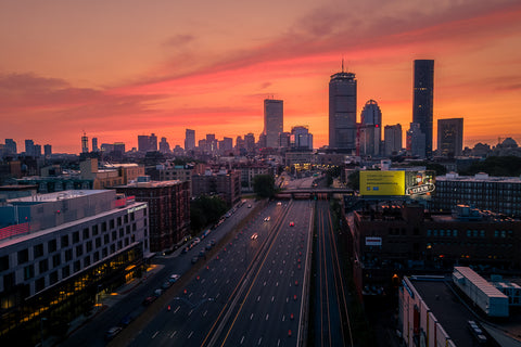 Boston skyline at sunrise, with an empty Mass Pike in front of it