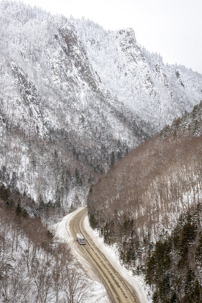 Looking down at a road through mountain pass during a snowy hike into Dixville Notch State Park in Dixville Township, New Hampshire