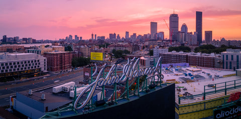 The Boston skyline looms behind the iconic John Hancock sign at Fenway Park