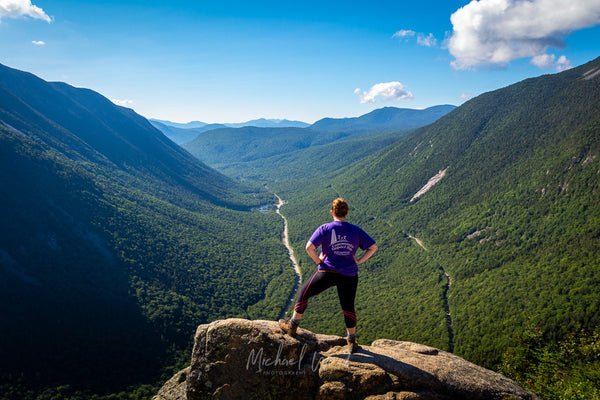 A hiker stands on top of a boulder looking out at Crawford Notch in the White Mountains of New Hampshire