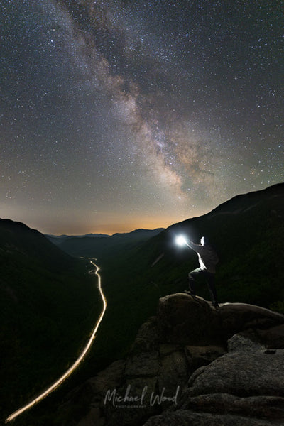 A hiker stands on top of a boulder as the Milky Way core rises over Crawford Notch in the White Mountains of New Hampshire