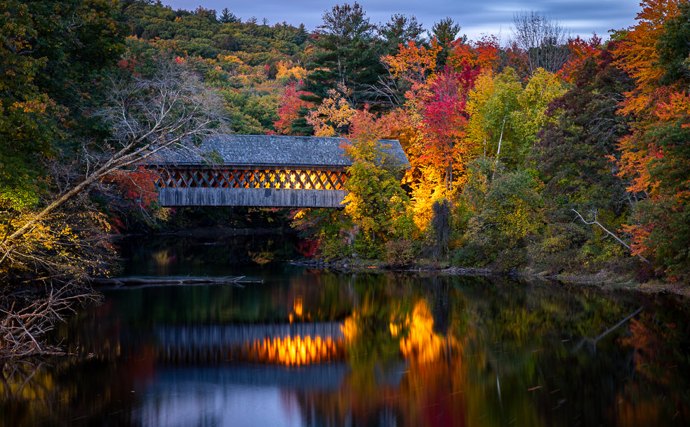 Fall foliage at sunrise at Henniker Covered Bridge in New Hampshire