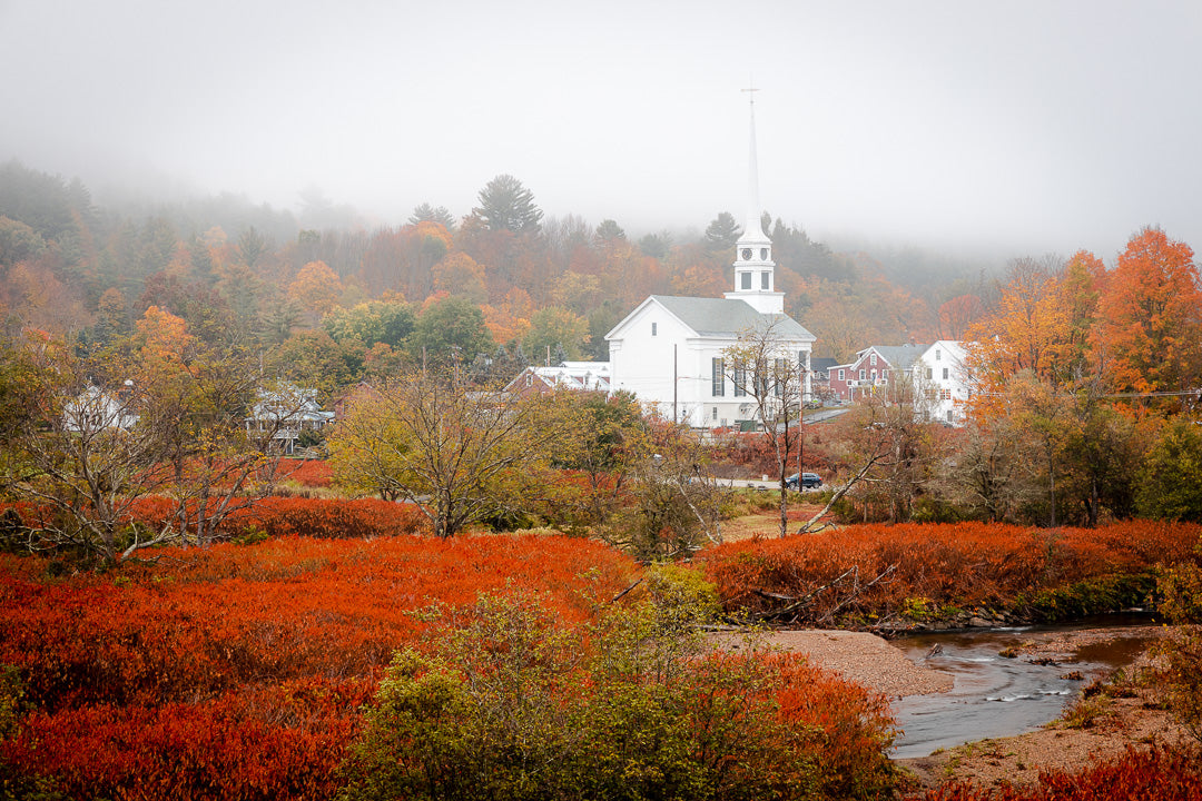 A view of Downtown Stowe, Vermont and the Little River during peak foliage