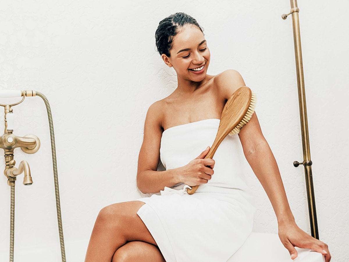 Women wearing a towel and dry brushing her arm