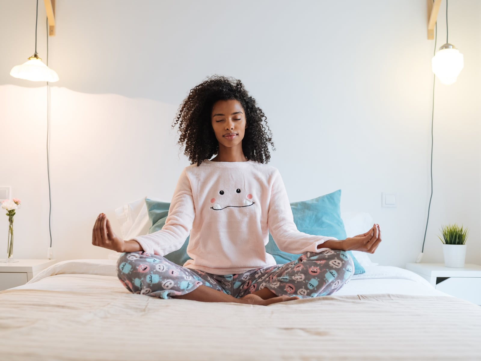 Woman of Color Meditating on a Bed | Metanoia Wellness