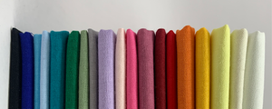 A rainbow of bright, plain cotton fabrics stack sideways..