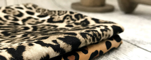 A pair of brown-toned animal print cottons on a grey wooden floor, with 2 oversized wooden bobbin/spools out of focus in the background.