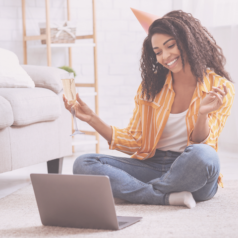 Black woman sitting on floor with laptop enjoying a beverage in a champagne flute during Wellness Hour