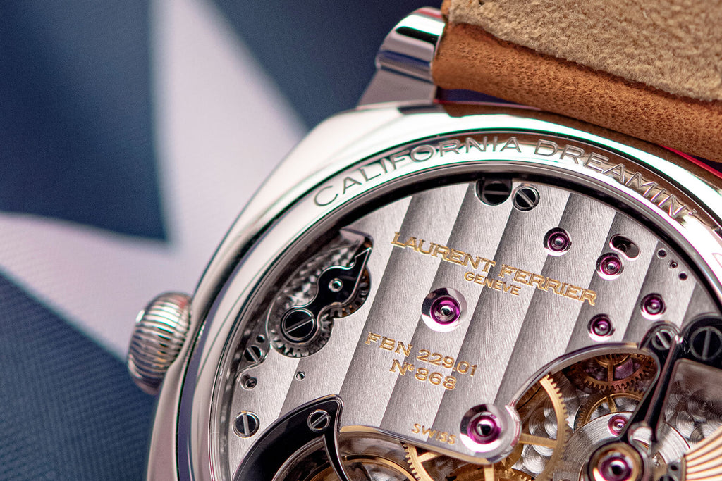 """Back view of Laurent Ferrier FBN 229.01 highly finished movement in Square California's US-exclusive stainless steel Square watch with """"California Dreamin'"""" engraved at the top of case back, United-States flag with navy and white blue star on the background."""