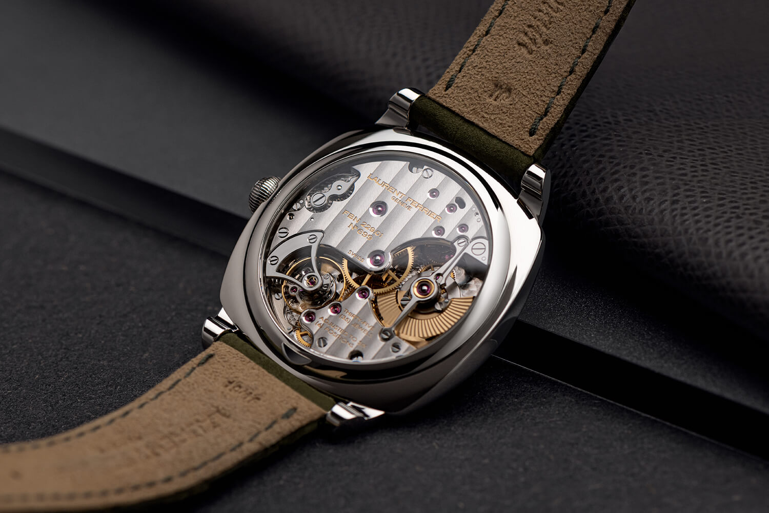 Stainless steel version of the watch resting on it's back showing a highly hand finished 229.01 micro-rotor movement through sapphire case-back.