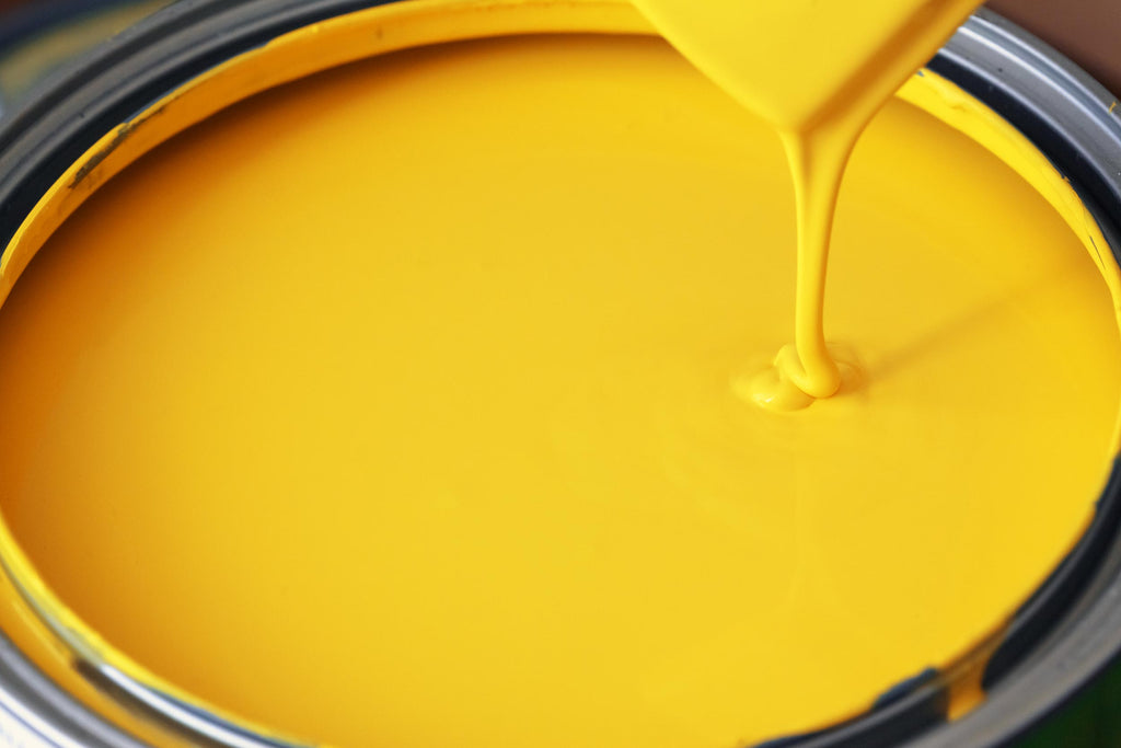 Close up of open yellow paint can