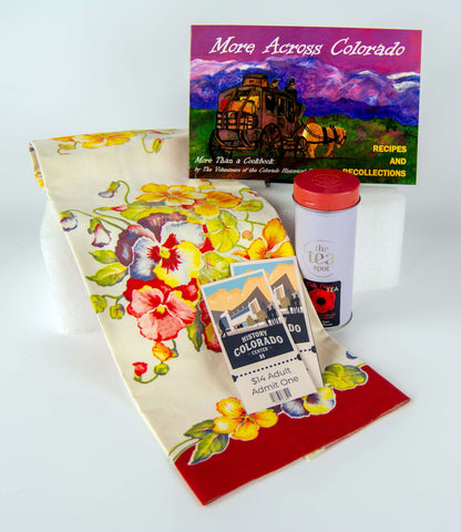 A unique curated bundle from the History Colorado Shop includes A vintage tea towel from the curator's own collection, Lady Evans tea, the More Across Colorado Cookbook, and two tickets to the History Colorado Center