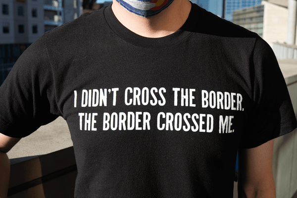 "The black Borderlands of Southern Colorado T Shirt front says ""I didn't cross the border, the border crossed me"" and Borderlands of Southern Colorado El Pueblo History Museum logo on back."