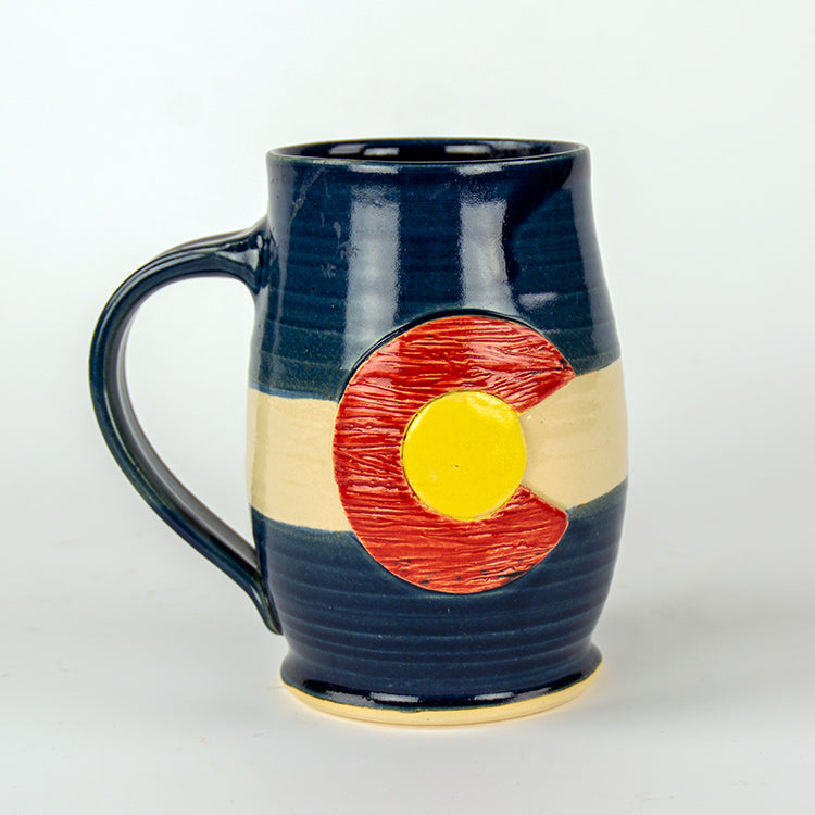 A dark blue handmade pottery coffee mug with a handle. Front features a textured colorado flag design.