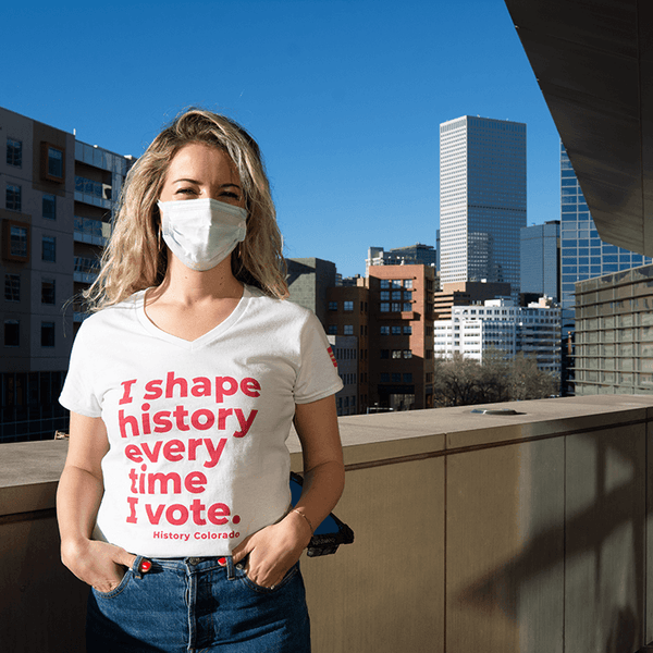 "A white, v-neck T Shirt front says ""I shape history every time I vote"" in pink writing on front. Sleeve has small Women's Vote Centennial / Colorado 2020 logo."