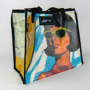 A bright colored limited edition banner tote bag with an illustration of a woman in retro sunglasses from History Colorado's Beer Here exhibition available in the History Colorado Shop