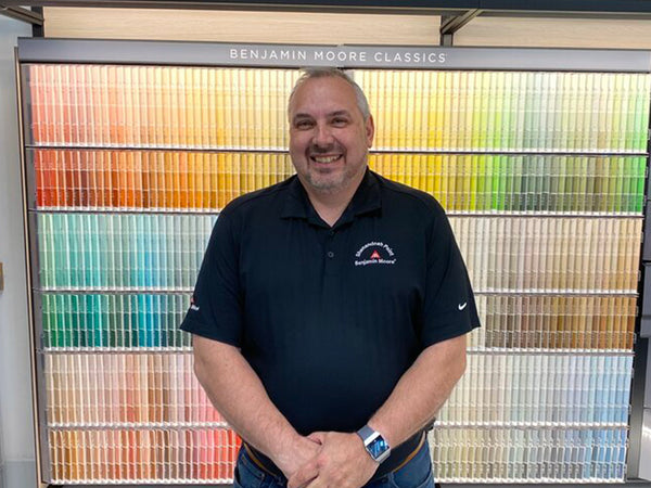 man in black shirt standing in front of wall of color samples