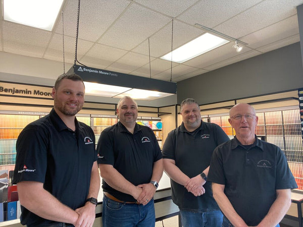 four men in black shirts standing inside paint store