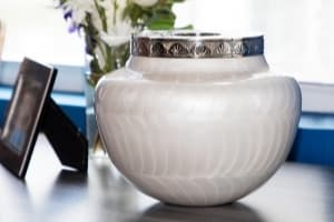 white cremation urn for ashes displayed on table top with flowers and photo frame in background