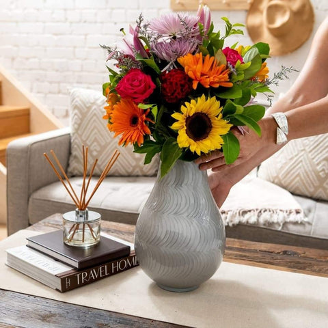 Extra Large cremation urn for ashes being displayed on table. Grey urn with colorful flower arrangement. Ladies hands placing vase down. sofa in background.  Home Decor shown