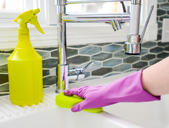 a rubber-gloved hand cleaning a sink near some cleaning fluid