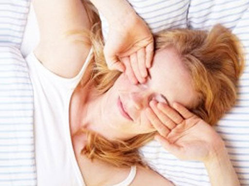 Woman waking up and rubbing her eyes