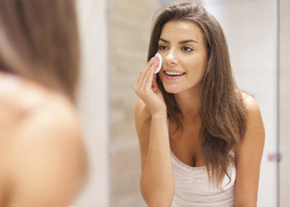Woman using a facial wipe in the mirror