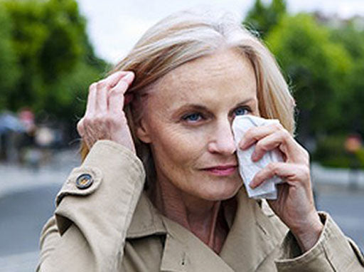 Woman wiping her eyes with a tissue