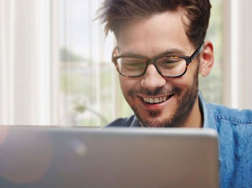 Man smiling and reading a monitor