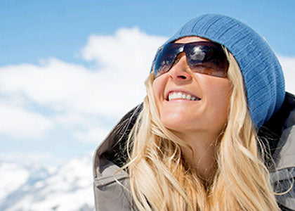 Woman in sunglasses, heavy coat, and knit hat