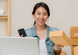 Asmiling woman with a phone and a package