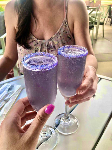 Two ladies holding champagne flutes with Lavendar French 75 cocktails embellished with Sugar Mama Shimmer edible drink glitter in Little Lilac and Violet Vibes. The champagne flute is rimmed in sugar and Sugar Mama Shimmer edible glitter for drinks.