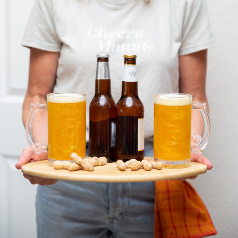 Woman holding football shaped charcuterie board with two beer steins, two bottles of beer, and peanuts.  The beer is glittery with Sugar Mama Shimmer Harlow Gold edible glitter for drinks.